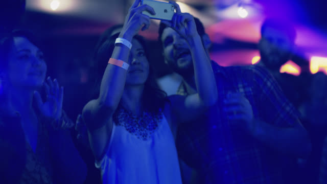 young woman in front row of concert takes a smartphone video of band as boyfriend watches - performance group stock videos & royalty-free footage