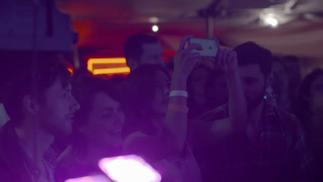 young woman in front row of rock concert records a video on her smartphone - enjoyment stock videos & royalty-free footage
