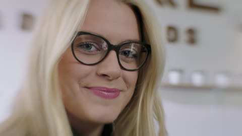 cu slo mo. young woman in glasses smiles at camera. - eyeglasses stock videos & royalty-free footage