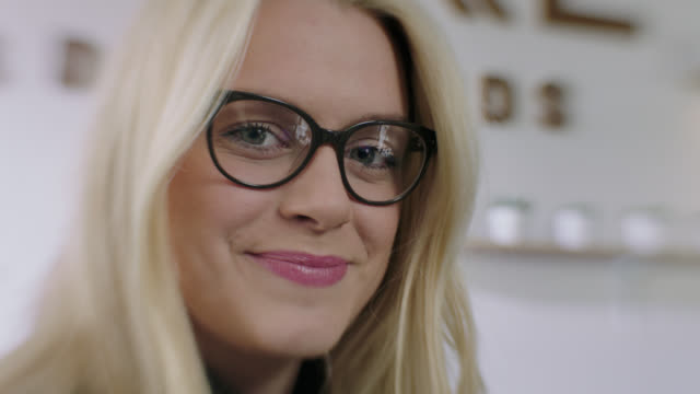 cu slo mo. young woman in glasses smiles at camera. - occhiali da vista video stock e b–roll