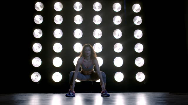 young woman in gym clothes does jumping jacks in front of wall of lights 4k - vesper stock stock videos & royalty-free footage