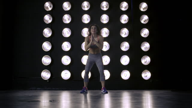 young woman in gym clothes does standing jumps in front of wall of lights 4k - vesper stock stock videos & royalty-free footage