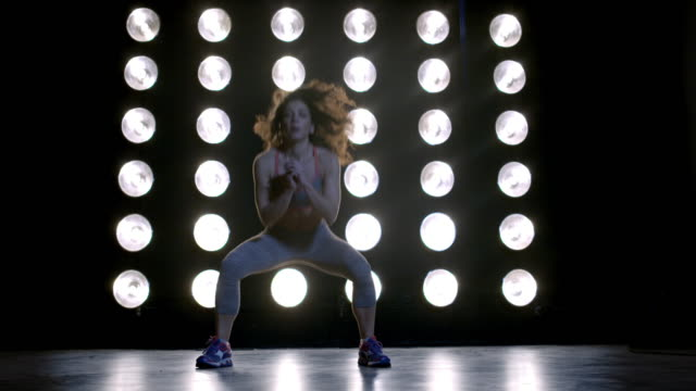 young woman in gym clothes steps and jumps in front of wall of lights 4k - vesper stock stock videos & royalty-free footage