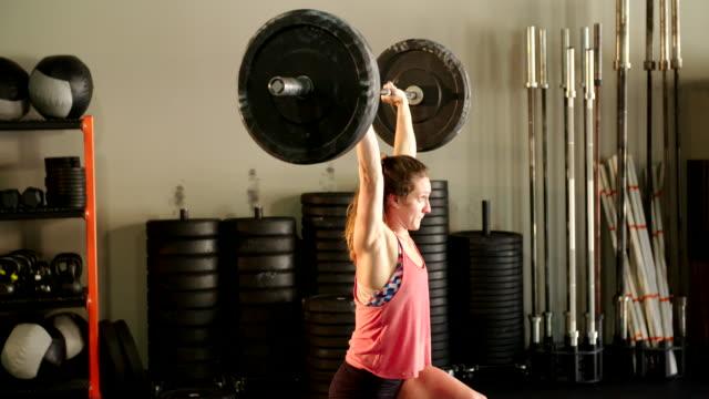 vídeos de stock, filmes e b-roll de jovem mulher na academia de ginástica - peso livre equipamento para exercícios