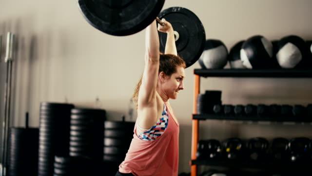 vidéos et rushes de jeune femme dans la salle de sport - musculation