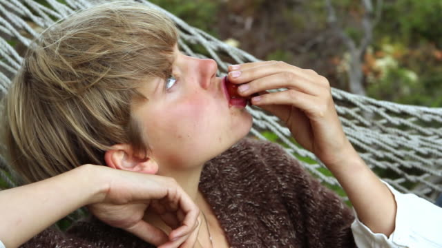 cu young woman in hammock eating juicy plum with juice dripping down from chin / big sur, california, usa - plum stock videos & royalty-free footage