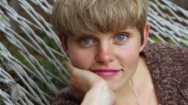 vidéos et rushes de cu young woman in hammock, smiling / big sur, california, usa - seulement des jeunes femmes