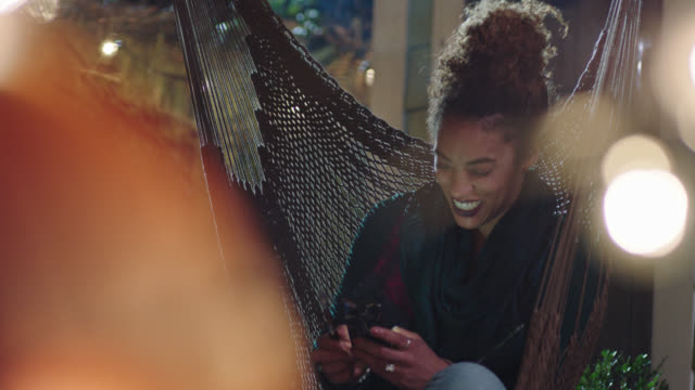 Young woman in hammock texts on smartphone and laughs while vaping.