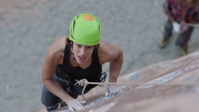 slo mo. young woman in harness smiles as she climbs steep rock face on moab adventure. - trust stock videos & royalty-free footage