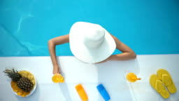 Young woman in hat chilling in swimming pool with tropical cocktail, vacation