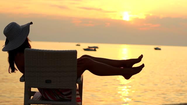 Junge Frau mit Hut sitzt am tropischen Strand