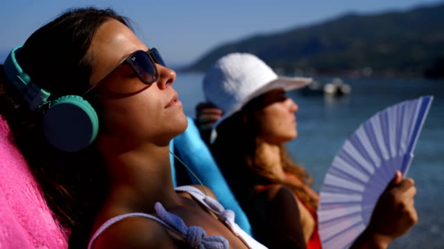 young woman in headphones listening music and enjoying beautiful views sea.close up - hand fan stock videos & royalty-free footage