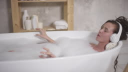 Young Woman in Headphones Singing while Taking a Bath