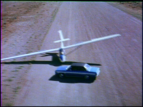 vidéos et rushes de a young woman in her '69 rambler rogue races her man on the airstrip as he lands his glider when the glider stops she gets out to give him a hug then... - 1960 1969