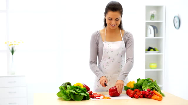 young woman in her kitchen cutting vegetables. - beautiful woman stock videos & royalty-free footage
