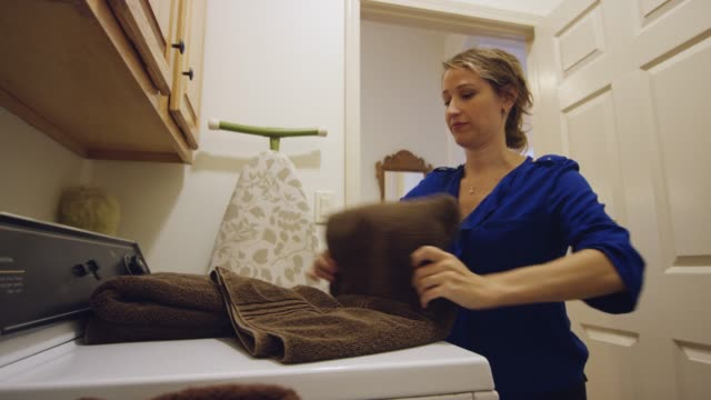 a young woman in her thirties folds towels in a residential laundry room - lavori di casa video stock e b–roll