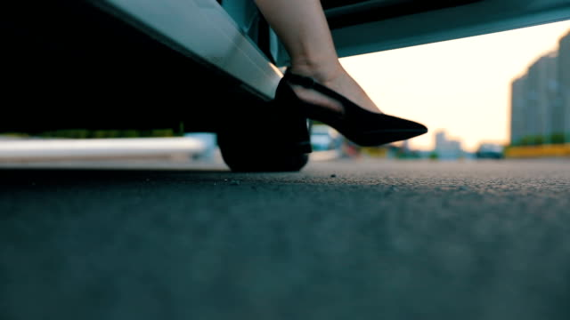 Young woman in high-heeled footwear stepping out of car