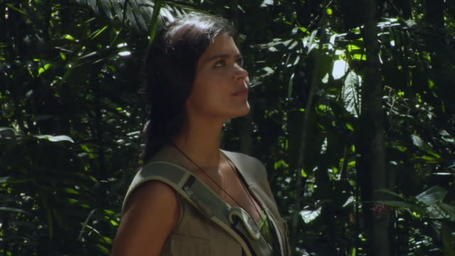 CU, Young woman in jungle looking through binoculars, Manaus, Brazil