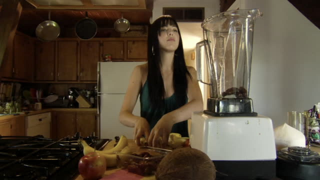 ms young woman in kitchen dancing as she cuts up banana and puts in in blender with soy milk to make a smoothie/ woman pouring blender contents into glass and exiting/ los angeles, california - soy milk stock videos and b-roll footage