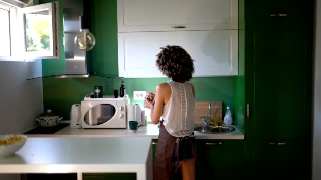 young woman in kitchen - cupboard stock videos & royalty-free footage