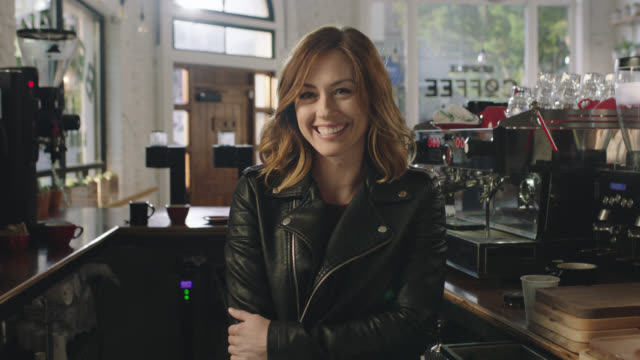 ms slo mo. young woman in leather jacket looks at camera and smiles behind bar in local independent coffee shop. - weibliche person stock-videos und b-roll-filmmaterial