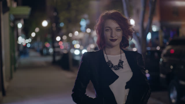 MS SLO MO. Young woman in leather jacket turns and stares at camera on city sidewalk at night.