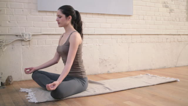 young woman in lotus position - lotus position stock videos & royalty-free footage