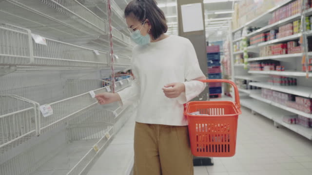 young woman in medical mask shopping during empty shelf - barren stock videos & royalty-free footage