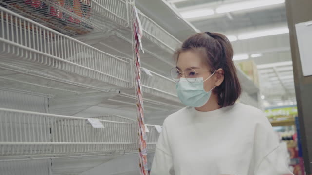 young woman in medical mask shopping during empty shelf - shelf stock videos & royalty-free footage