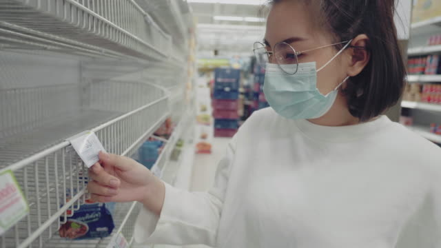 young woman in medical mask shopping during empty shelf - market retail space stock videos & royalty-free footage