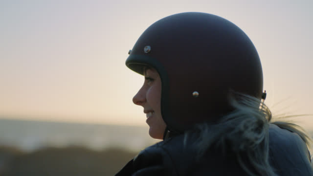 cu slo mo. young woman in motorcycle helmet looks out over the ocean and laughs. - スポーツヘルメット点の映像素材/bロール