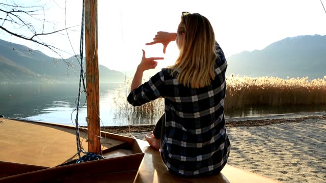 Young woman in nature framing mountain lake landscape with fingers