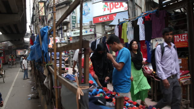 A young woman in niqab and child on her arm is shopping clothes on a fabric stand at the street while the busy traffic can be seen on the left side...