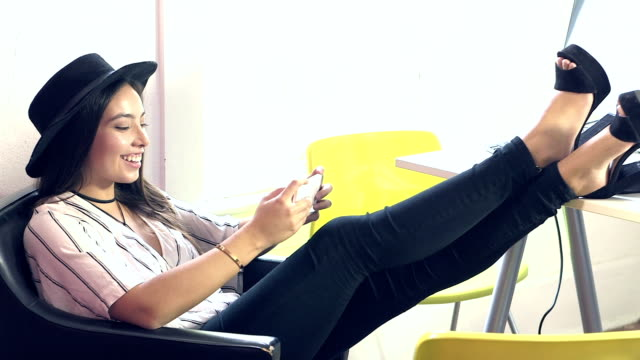 Young woman in office with feet up, using mobile phone