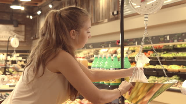 ms young woman in organic food store filling plastic bag with oranges and placing bag on weighing scale - scales stock videos & royalty-free footage
