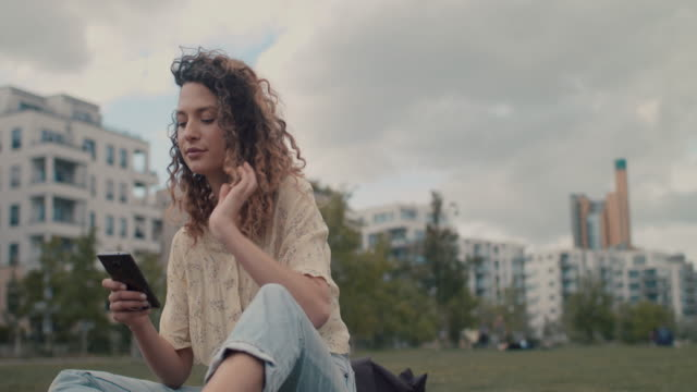 vidéos et rushes de young woman in park in central berlin looking at smart phone - vie citadine