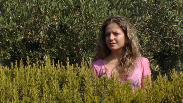 vídeos de stock e filmes b-roll de jovem mulher no parque olha para alguém e ondas mão - só meninas adolescentes
