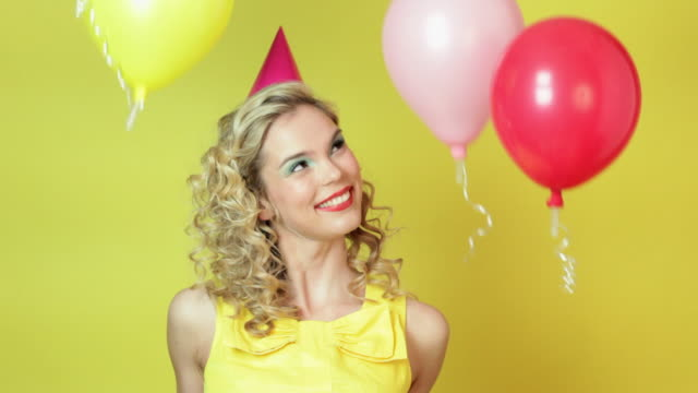 young woman in party hat and floating balloons - party hat stock videos & royalty-free footage