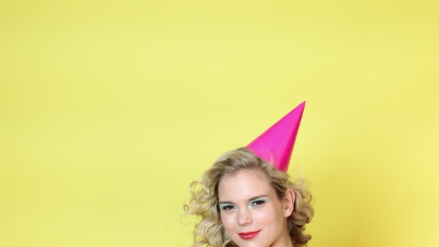 young woman in party hat blowing party horn blower - party hat stock videos & royalty-free footage