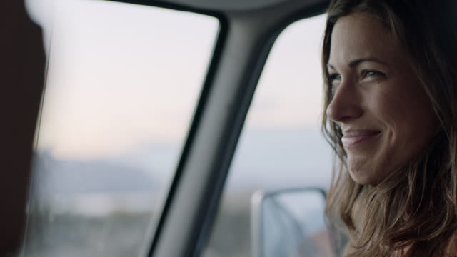 vidéos et rushes de cu. young woman in passenger seat turns to look at driver and smiles on moab road trip. - voyage