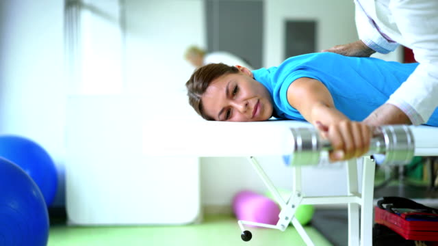 vídeos de stock, filmes e b-roll de jovem mulher na fisioterapia. - fisioterapeuta