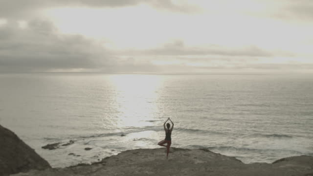 Young woman in Portugal by the ocean doing yoga