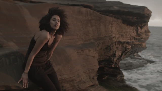 young woman in portugal by the ocean sitting on rocks at sunset - big hair stock videos & royalty-free footage