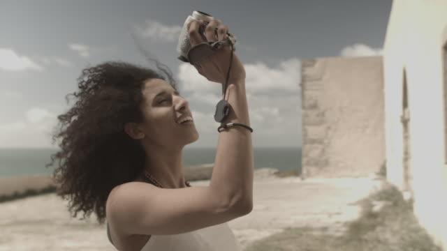 Young woman in Portugal exploring fort by the ocean, filming with small camera