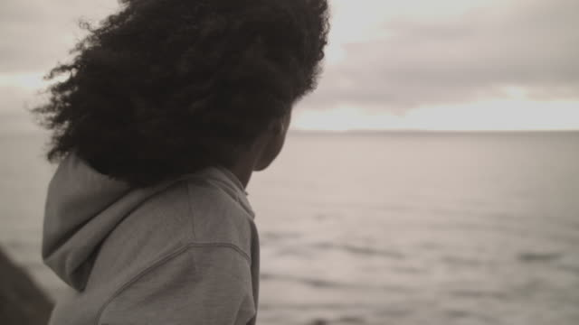 young woman in portugal looking out over the ocean at sunset - hood clothing stock videos and b-roll footage