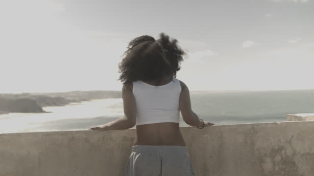 vídeos de stock, filmes e b-roll de young woman in portugal standing by stone wall at sea side enjoying wind and view - exposto pelo vento