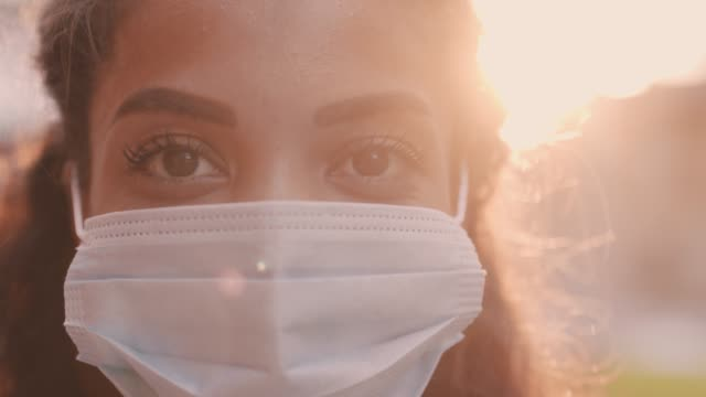 young woman in protective face mask contemplating and smiling - removing stock videos & royalty-free footage