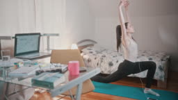 Young woman in quarantine taking a break from work and doing exercises