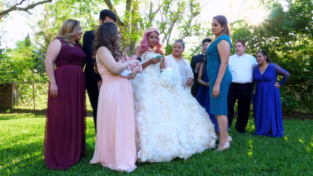 ms young woman in quinceanera gown looking at smartphone while standing with family in backyard - 14 15 anni video stock e b–roll