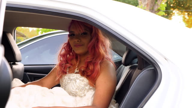 MS Young woman in quinceanera gown sitting in back seat of car